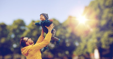 family, childhood, fatherhood, leisure and people concept - happy father and little son playing and having fun outdoors over summer park background