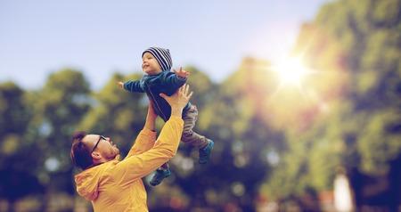 jovenes felices: la familia, la infancia, la paternidad, el ocio y el concepto de la gente - feliz padre e hijo poco de juego y divertirse al aire libre sobre el fondo del parque del verano