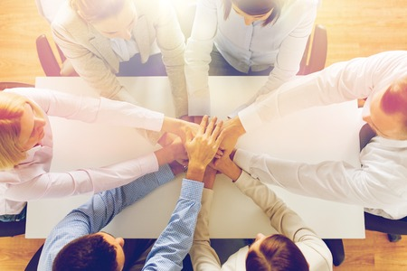 negocio, la gente, la cooperación y el trabajo en equipo concepto - cerca de equipo creativo sentado en la mesa y la mano en la parte superior de uno al otro en la oficina Foto de archivo