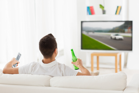 motorsports: sport, leisure, technology, motorsports and people concept - man watching car racing on tv and drinking beer from bottle at home from back Stock Photo