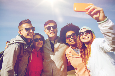 family and friends: people, leisure, friendship and technology concept - group of smiling teenage friends taking selfie with smartphone outdoors