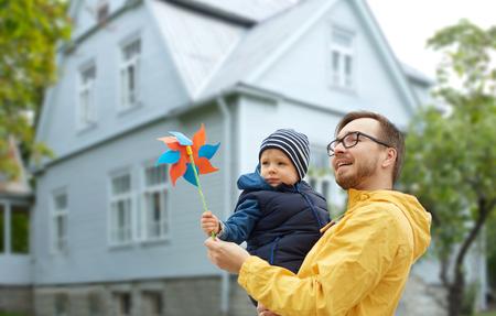 家族、子供、父権、レジャーと人コンセプト - 幸せな父と生活上屋外風車おもちゃで幼い息子家背景 写真素材