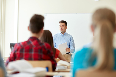 school exam: education, school, learning and people concept - group of students and teacher with tests in classroom