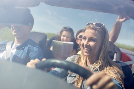 driving a car: leisure, road trip, travel and people concept - happy friends driving in cabriolet car along country road