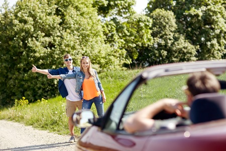 road trip, hitchhike, travel, gesture and people concept - happy couple hitchhiking and stopping car at countryside road Stock Photo