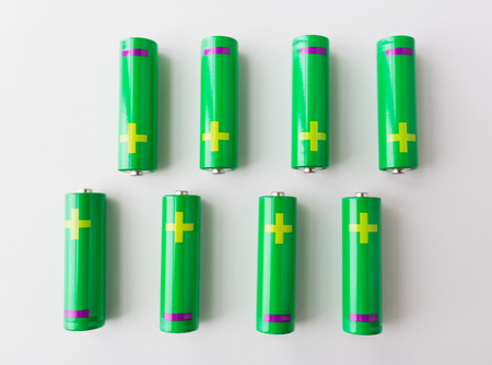 recycling, energy, power, environment and ecology concept - close up of green alkaline batteries Stock Photo