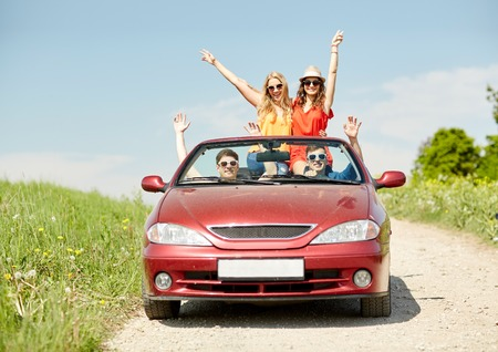 country road: leisure, road trip, travel and people concept - happy friends driving in cabriolet car at country and waving hands