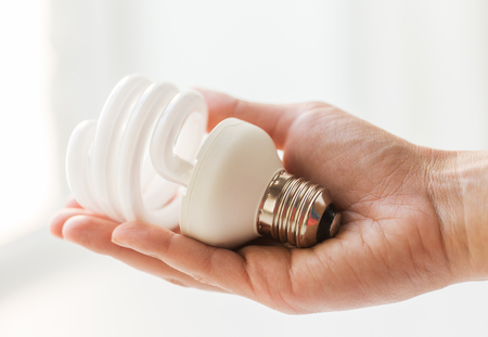 fluorescent: recycling, electricity, environment and ecology concept - close up of hand holding energy saving lightbulb or lamp Stock Photo