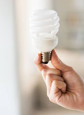 utilization: recycling, electricity, environment and ecology concept - close up of hand holding energy saving lightbulb or lamp Stock Photo
