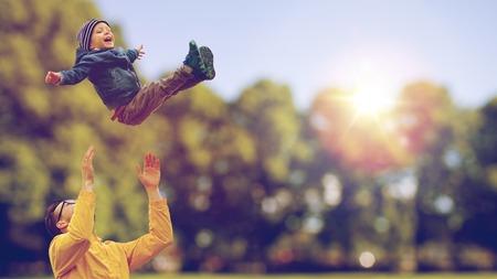 familie, jeugd, vaderschap, vrije tijd en mensen concept - gelukkige vader en zoontje spelen en plezier buitenshuis op zomer park achtergrond