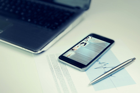 social web: business, technology, social media and network concept - close up of smartphone with web page on screen, laptop computer and chart with pen on office table Stock Photo