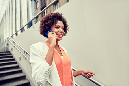 bajando escaleras: negocio, la comunicación, la tecnología y el concepto de la gente - joven sonriente africano americano de negocios que invita al teléfono inteligente bajar escaleras en paso subterráneo de la ciudad Foto de archivo