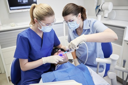 treating: people, medicine, stomatology and health care concept - female dentist and assistant with dental curing light and mirror treating male patient teeth at dental clinic office