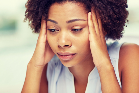 unhappy people: people, emotions, stress and health care concept - unhappy african american young woman touching her head and suffering from headache