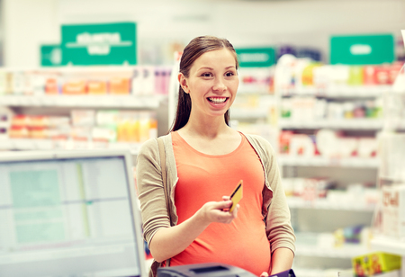pharmaceutics: medicine, pharmaceutics, health care and people concept - happy pregnant woman with credit card in at cashbox drugstore Stock Photo