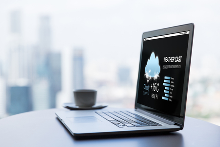 technology, weather cast, business and modern life concept- close up of open laptop computer with meteo forecast on screen and coffee cup on table at office or hotel room Stock Photo