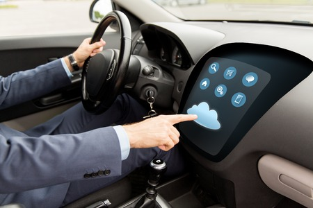 transport, business trip, modern technology and people concept - close up of man driving car with menu on board computer screen and cloud icon