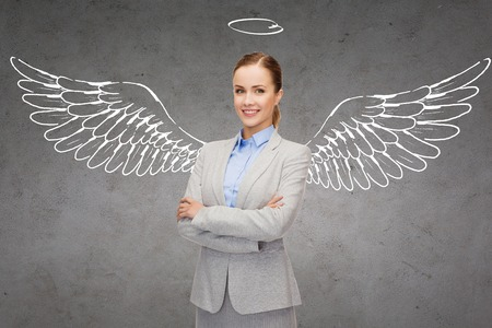 angel: business, angel investor, safety, security and people concept - smiling young businesswoman with wings and nimbus drawing over gray concrete background