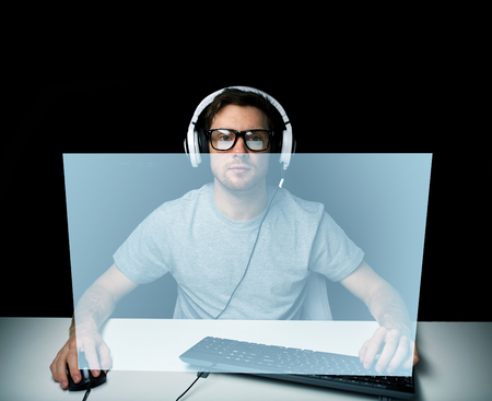 cyber terrorism: technology, gaming, lets play and people concept - young man or hacker in headset and eyeglasses with pc computer playing game and streaming playthrough or walkthrough video with virtual screen Stock Photo