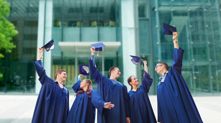 academic robe: education, graduation and people concept - group of smiling students in gowns waving mortarboards over school or university building background