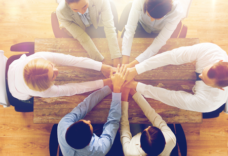team cooperation: business, people, cooperation and team work concept - close up of creative team sitting at table and holding hands on top of each other in office Stock Photo