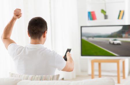 motorsports: leisure, technology, motorsports, sport and people concept - man with remote control watching car racing on tv at home