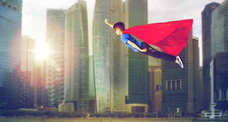 air movement: happiness, freedom, childhood, movement and people concept - boy in red superhero cape and mask flying in air over singapore city skyscrapers background