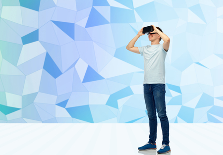 3d technology, virtual reality, entertainment, cyberspace and people concept - happy young man with virtual reality headset or 3d glasses over low poly background