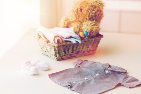 babyhood, motherhood, clothing and object concept - close up of baby clothes and toys for newborn boy in basket at home Stock Photo