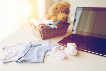 babyhood: babyhood, motherhood, clothing, technology and object concept - close up of baby clothes and toys for newborn boy in basket with laptop computer at home