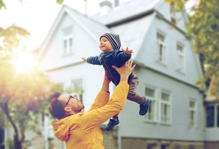 familj: Familj, barndom, faderskap, fritid och människokoncept - glad pappa och lilla son leker och ha kul utomhus över levande husbakgrund Stockfoto