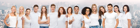 men and women: diverse, gesture and people concept - group of happy different body size and age and gender people in white t-shirts hugging showing thumbs up over city background