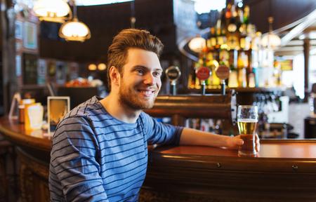 hombre tomando cerveza: la gente, las bebidas, el alcohol y el concepto de ocio - joven feliz cerveza hombre bebiendo en el bar o pub Foto de archivo