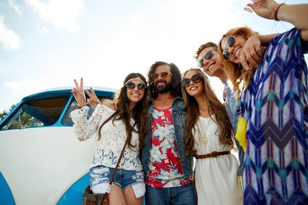 minivan: summer holidays, road trip, vacation, travel and people concept - smiling young hippie friends over minivan car showing peace hand sign Stock Photo