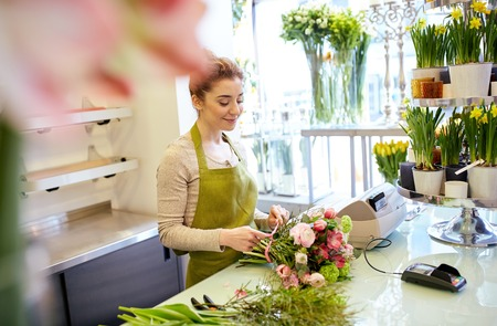 sale shop: people, business, sale and floristry concept - happy smiling florist woman making bunch at flower shop
