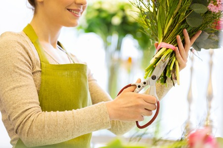 cropping: people, business, sale and floristry concept - close up of florist woman making bunch and cropping stems by scissors at flower shop