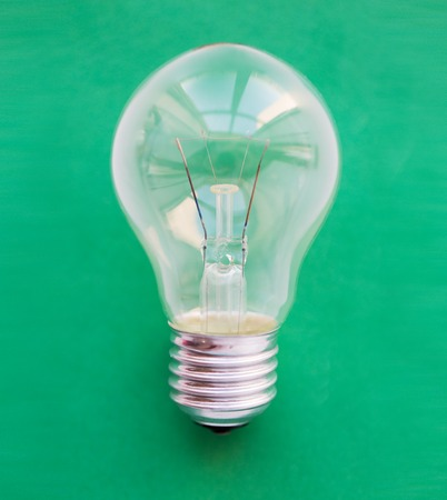 saving electricity: recycling, energy saving, electricity, environment and ecology concept - close up of lightbulb or incandescent lamp on green