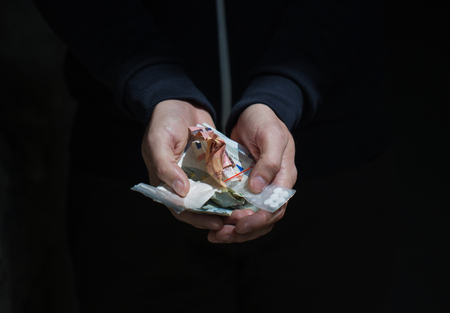 drug trafficking: drug trafficking, crime, addiction and sale concept - close up of addict hands with drugs and money