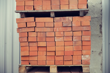 batch: brickwork, construction and building material concept - brown bricks batch on wooden storage tray