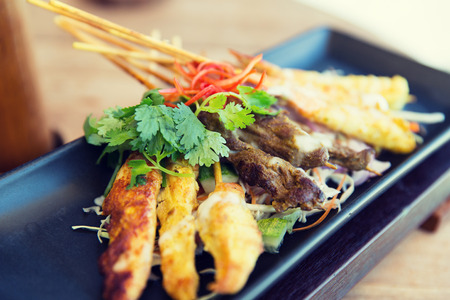 japanese cooking: asian kitchen, food, culinary and cooking concept - close up of deep-fried snacks on plate at restaurant