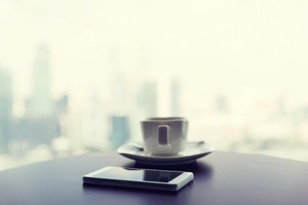 hotel room: technology, business and modern life concept- close up of smartphone and coffee cup on table at office or hotel room