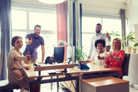 latin man: business, startup and people concept - happy creative team showing thumbs up in office