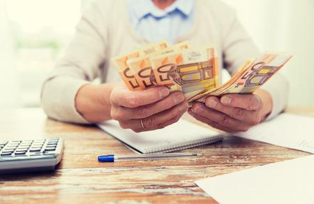 contaduria: negocio, ahorros, seguros de rentas, la edad y el concepto de la gente - cerca de la mujer mayor con la calculadora y contar billetes de euros de dinero en casa Foto de archivo