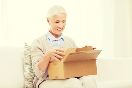 delivery room: age, delivery, mail, shipping and people concept - happy smiling senior woman looking into open parcel box at home