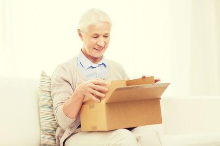sala parto: l'età, la consegna, la posta, il trasporto e la gente concetto - felice donna senior sorridente cercando in scatola di pacchi aperti a casa Archivio Fotografico