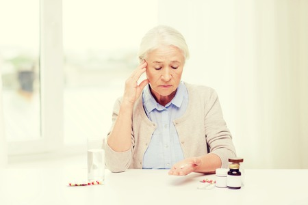 age, medicine, health care and people concept - senior woman with pills and glass of water at home Stock Photo