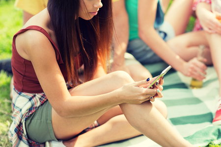 women sitting: travel, tourism, picnic, technology and people concept - close up of young woman or teenage girl texting on smartphone with friends outdoors Stock Photo