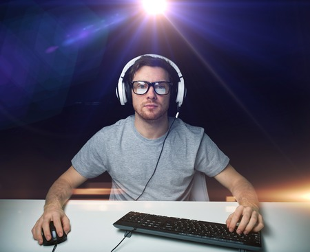 technology, gaming, entertainment, lets play and people concept - young man in headset and eyeglasses with pc computer playing game and streaming playthrough or walkthrough video over light