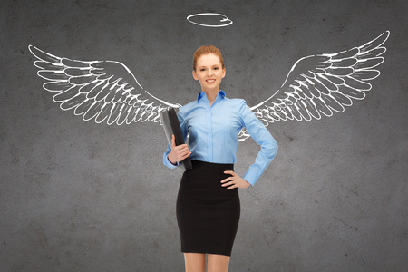 business, angel investor, safety, security and people concept - smiling young businesswoman with wings and nimbus drawing over gray concrete background photo