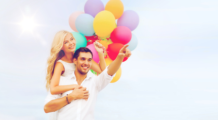 summer holidays, celebration and dating concept - couple with colorful balloons at sea side photo